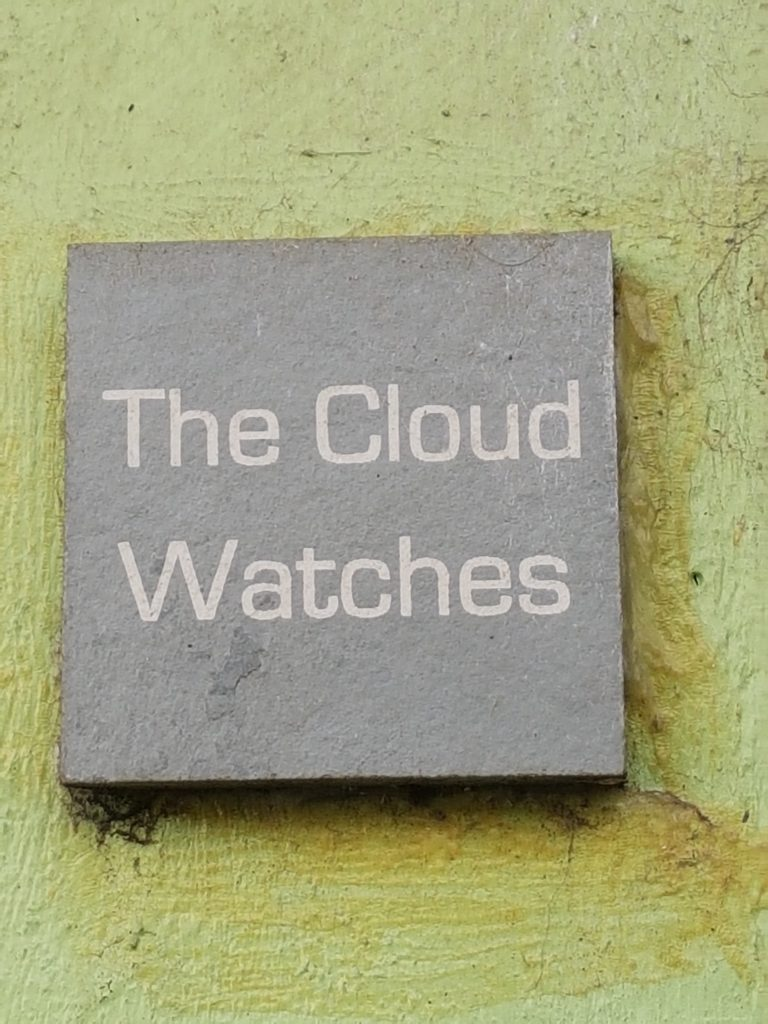 """A slate sign on a yellow wall that reads """"The Cloud Watches"""""""