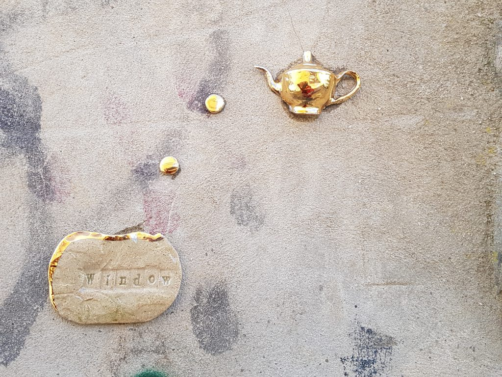 """the image shows a golden teapot stuck to a wall above a stone reading """"window"""" on it."""