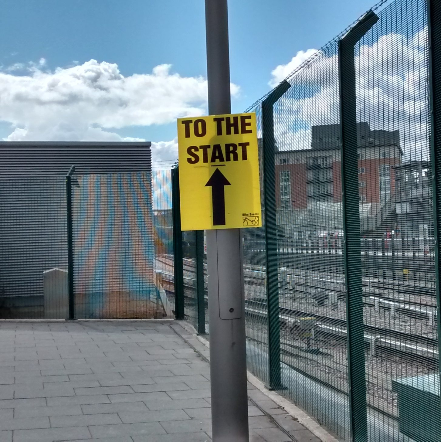"the image shows a yellow sign attached to a lamppost in an urban environment. The sign reads ""to the start"" with an arrow pointing forwards."