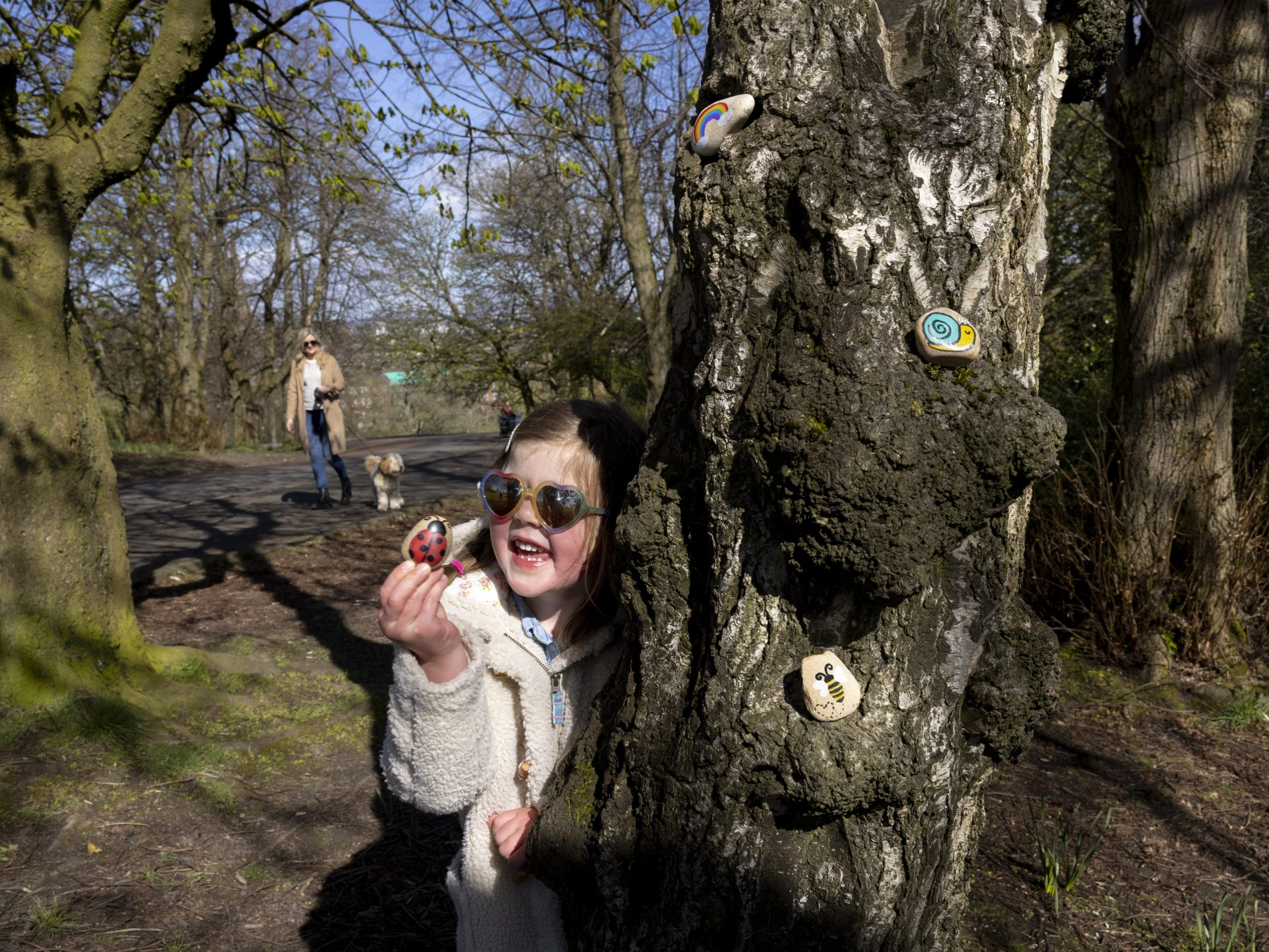 The image shows young girl searching for painted stones in a wooded area.
